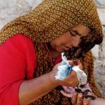 Femme marocaine dessinant sur la peau à l'henné.