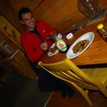Etienne goûte au bonheur du voyageur. L'extase face aux plaisirs simples : pancake + sirop d'érable, assis à une table et à l'abri du froid.