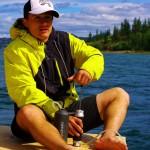 Brian filtre de l'eau pour l'équipe. Sur le Yukon, il suffit de plonger l'embout du filtre dans l'eau du fleuve et de pomper pour obtenir de l'eau fraîche et potable. Pas tout à fait claire par endroits, le filtre s'encrasse vite et nous devons le nettoyer chaque jour.
