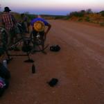 Petite pause forcée en route pour l'Oodnadata track. La roue arrière du vélo d'Etienne vient de crever. Avec une certaine habitude maintenant, nous enlevons toutes les sacoches, retournons le vélo et réparons la crevaison en un éclair. Les autres profitent du coucher du soleil pour contempler le paysage et se restaurer un peu.