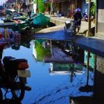 Lorsque la marée est haute, l'eau monte jusque dans les rues du village. Ici une photographie d'une scène quotidienne typiquement thaïe. L'accoutrement des cyclistes en particulier donne le sourire.