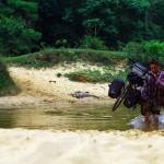 Voie sans issue ? Non non, il suffit juste de traverser la rivière, avec de l'eau jusqu'aux genoux, pour rejoindre la piste en face. Afin d'éviter de faire prendre l'eau à ses sacoches, Brian doit porter son vélo chargé.
