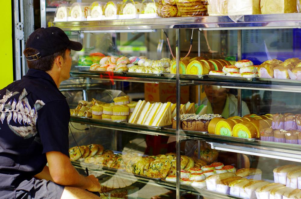 Alors que nous nous apprêtons à quitter la ville de Pleiku, nous tombons nez à nez avec cette boulangerie. Voilà bien longtemps que nous n'avons pas eu le plaisir de gouter à de telles viennoiseries… Ici Morgan est en train de montrer à la vendeuse ce qu'il souhaite acheter. Pour 0,25euros, on peut se faire ce petit plaisir au Vietnam.