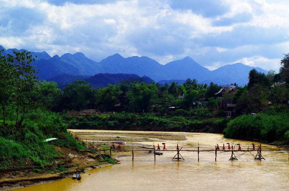 Une autre vue de Luang Prabang. Ce pont en bambou relie la péninsule à la zone nord de la ville. En premier plan les moines qui utilisent leur parapluie comme parasol. Au fond on aperçoit les montagnes que nous avons traversé avant d'arriver dans cette ville. Ce sont ces barrières naturelles qui ont protégé la cité des envahisseurs pendant de nombreuses années et qui ont permis à Luang Prabang de conserver son aspect originel.