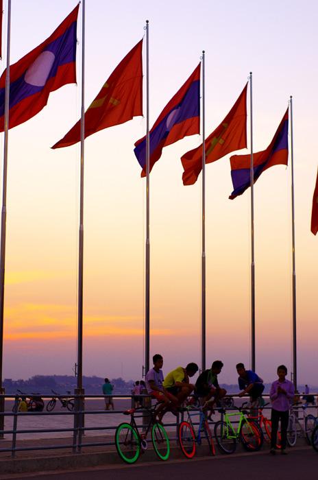 Vientiane. Nous voilà enfin dans une grande ville laotienne après 800 kilomètres depuis le Vietnam. Pour une superficie de prêt de la moitié de la France on ne compte que 2 grandes villes et guère plus de 6,5 millions d'habitants. État voisin de la Chine, la majorité des produits viennent de là-bas. Il est donc difficile de ne pas tomber sur de parfaites contrefaçons, pour les vêtements, les nouveautés électroniques, mais aussi les équipements sportifs. Sur cette image ce sont des vélos « fixie » made in china. De parfaites copies des modèles très tendances à San Francisco par exemple. Mais malheureusement leur durée de vie est courte et ils ne brilleront pas longtemps… De même que la télévision, ces produits font vivre certain jeunes laotiens dans un monde d'illusion où les besoins qu'ils se créent ne correspondent pas à ceux de leur société ni de leur culture.