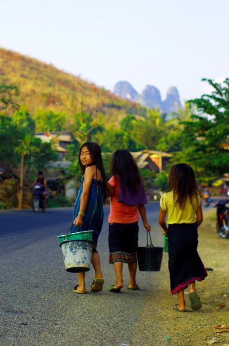 Scène classique en fin de journée sur les bords de route aux abords des villages. Ici trois jeunes filles d'une dizaine d'années, totalement autonomes, reviennent de la rivière où elles ont pu se laver à l'eau fraîche ainsi que faire une petite lessive.