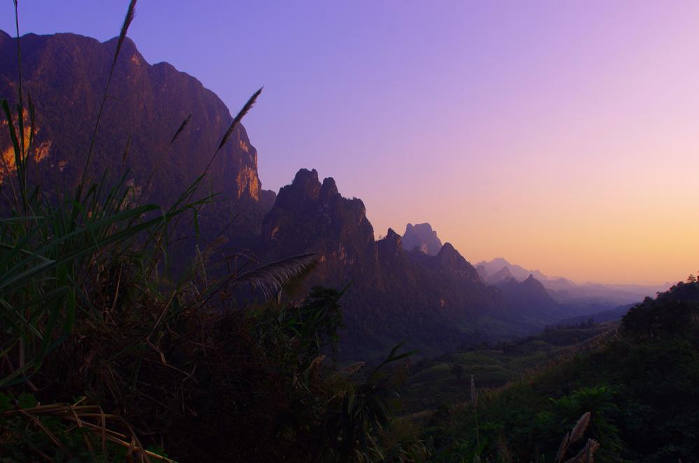 Non loin de Vang Vieng. Nous voilà de nouveau à évoluer dans des montagnes splendides. Prendre de la hauteur à vélo vous fait certes suer, mais c'est ce qui fait qu'on apprécie la vue à sa juste valeur. Quand, en plus, le tout se passe au coucher du soleil, alors les couleurs s'en mêlent et le spectacle commence !