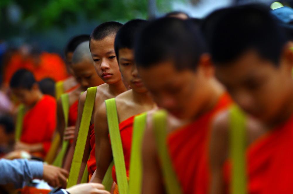 Le Tak Bat C'est l'expression profonde de la générosité, une vertu cardinale pour le peuple lao et une source particulière de mérites religieux pour les fidèles bouddhistes. Ce rite constitue probablement le lien le plus étroit entre les laïcs et les moines. Il est toujours pratiqué avec une profonde conscience de sa beauté, avec ferveur, concentration, sérieux et une grande implication. La plupart des bouddhistes de Luang Prabang font cette offrande chaque matin. Tôt le matin, on prépare dans ce but du riz cuit le jour même. Les fidèles se mettent à genoux, pieds nus par humilité sur une natte et attendent la file des bonzes (moines). Ils déposent rapidement en silence et les yeux baissés un peu de riz dans le bol à aumône de ces derniers. Plus rarement gâteaux et fruits sont offerts. Les fidèles accomplissent avec joie cet acte généreux dont les bienfaits rejailliront sur eux-mêmes, sur leurs proches en vie ou disparus et sur tous les êtres vivants. De leur côté les bonzes méditent sur l'impermanence et sur le sens de ces offrandes qui symbolise leur pauvreté, leur humilité et leur dépendance volontaire de la communauté des laïcs pour leurs besoins matériels. De retour à la pagode, les bonzes partageront ce riz, accompagné de plats apportés par les fidèles. Ils prendront ce premier repas de la journée en silence. (source : http://www.apsaraventure.com/)
