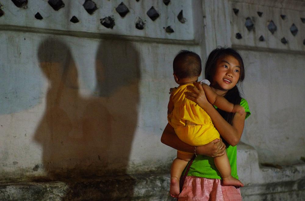 La grande sœur veille sur son petit frère. Le petit était allongé sur le trottoir, sur une couette à l'abri d'une moustiquaire, où il s'endormait tandis que sa mère vendait ses produits au marché de nuit. Puis, peut être réveillés par un vilain cauchemar, sa sœur est venue le prendre dans ses bras pour le consoler.