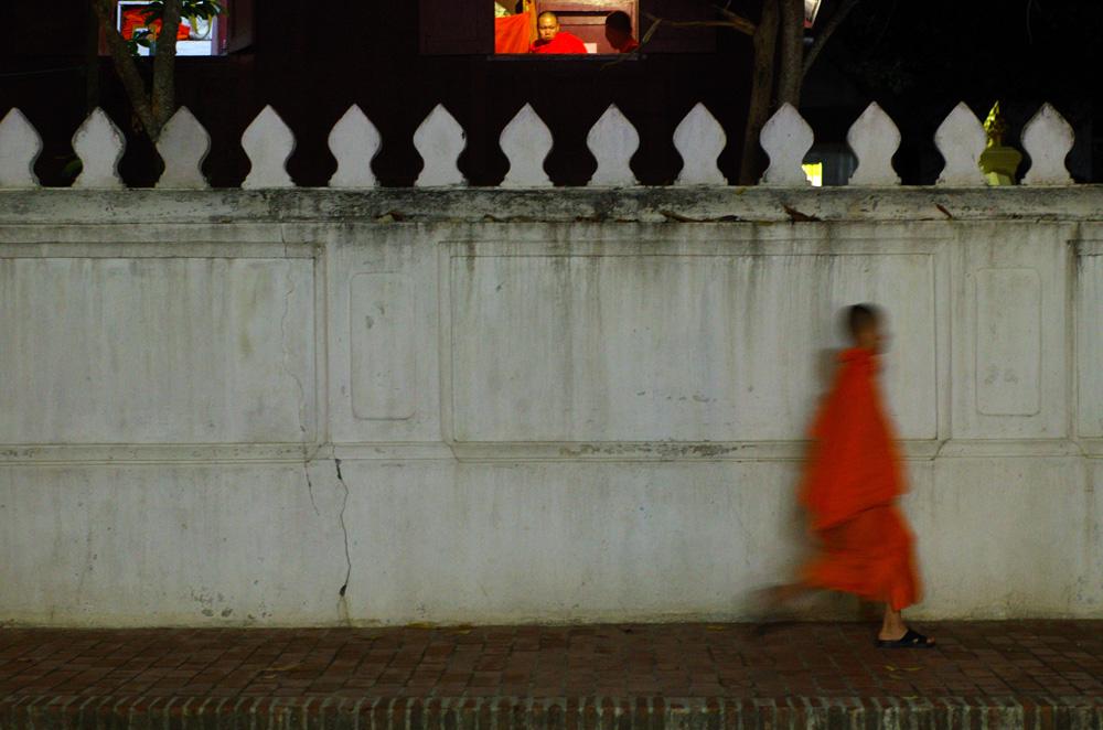 Il est déjà 21 h et les moines ont un rythme de vie très strict, se lèvent très tôt, méditent et prient de longues heures le jour durant. C'est donc le moment de rentrer au « Wat » temple … Sur le haut de la photographie, on aperçoit un maître bouddhiste guettant ces jeunes élèves, même si l'heure n'est pas la première des priorité au Laos, celui-ci serait t-il un peu en retard ?