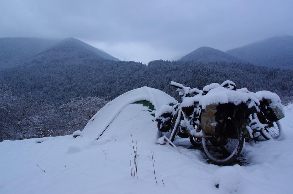 Réveil surprise ! Une couche assez épaisse de neige s'est abattue sur la tente et nos vélos. Nous ne sommes pas équipés pour ce genre de conditions et ne portons qu'un simple paire de tennis au pied... Nous sortons de la tente en essayant de ne pas trop mouiller nos pieds... et espérons que le passage du col aujourd'hui se fera sans encombre.