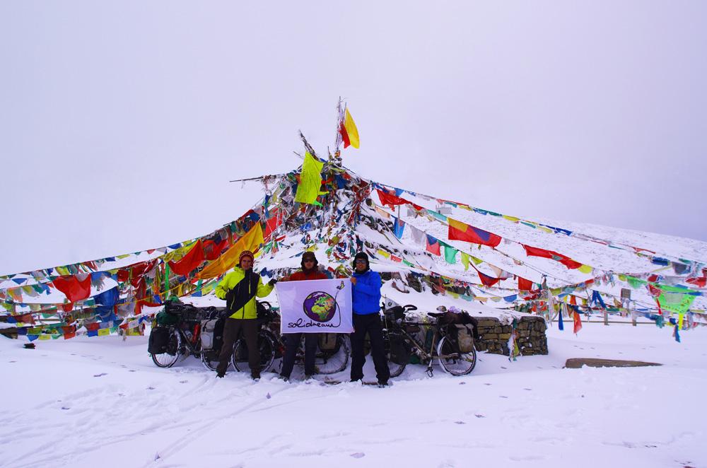 Au sommet, nous prenons la pause sous les loungtas, ces drapeaux de prière colorés typiques des régions voisines de l'Himalaya, malgré nos extrémités engourdies par le froid. Le rêve est réalisé : nous sommes avec nos vélos en haut d'une montagne de l'ancien Tibet à 4000m d'altitude. Dans nos têtes, nous faisons la nique à tout ce foutoir administratif qui a bien failli nous faire rater cet instant. La vue n'est pas parfaite, mais qu'importe, nous sommes au sommet. Pas seulement le sommet de notre itinéraire, mais aussi celui d'un cheminement de pensée en phase avec nos valeurs : celui de croire à un rêve et de persévérer pour le réaliser.