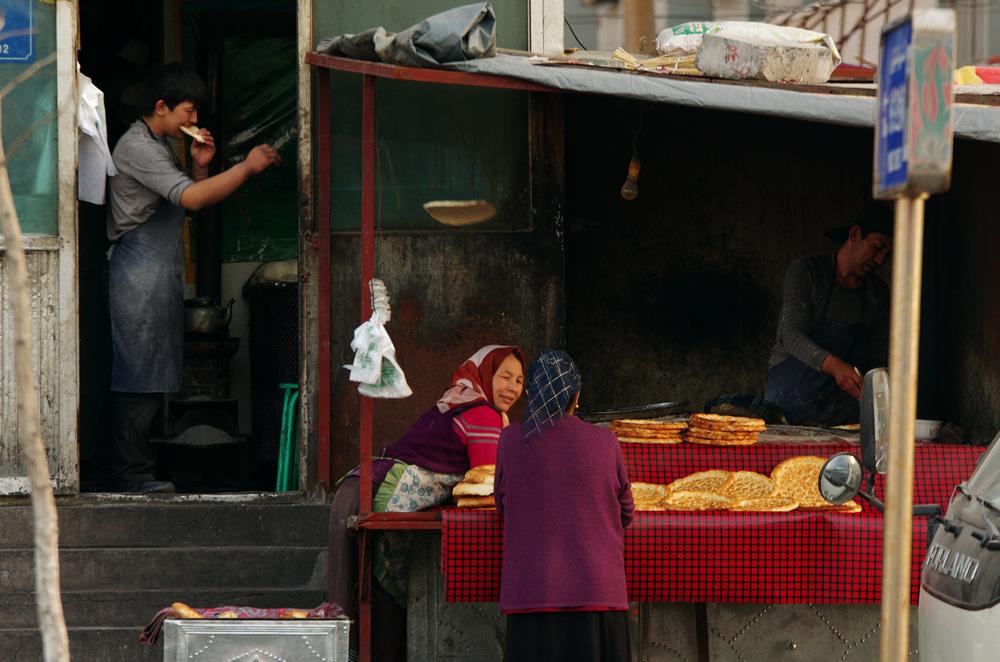 Le père et son fils forment un beau duo. Le « nan » coûte 2 Yuan (0,25€), il faut donc en produire une grande quantité pour en vivre. Les clients défilent non stop tandis que nous admirons la dextérité de ces boulangers de rue. Le plus jeune, une fois la galette prête à cuire, la jette comme un frisbee sur la table de son père qui s'occupe ensuite de la cuisson.