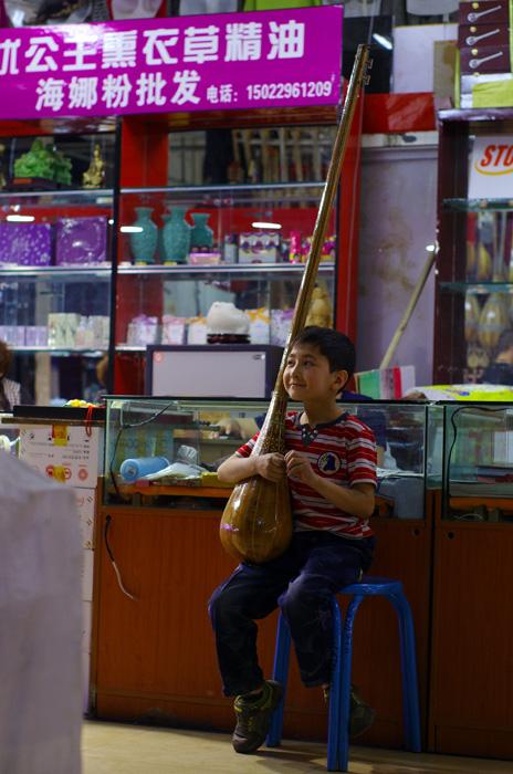 Puisqu'il faut patienter pendant le processus des visas kazakhs, nous entamons les visites touristiques, chose que nous faisons que très rarement depuis ces 2 ans et 8 mois. Voici le Marché Erdaoqiao, où l'on peut y trouver toute sorte de vêtements et d'artisanats Ouïgours. Urumqi n'est pas une ville très fréquentée par le tourisme international. À notre venue, des vendeurs encouragent le jeune prodige à montrer ses talents. Il se lance alors, après a avoir minutieusement choisi son instrument, pour 5 minutes de remarquable mélodie. Les sourires se dessinent sur les visages de toutes les personnes assistant au spectacle improvisé !