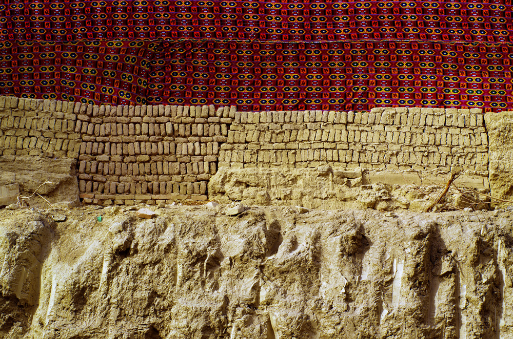 Les maisons en briques de terre pour assurer un minimum d'isolation thermique. Ce mur en l'occurrence ne fait pas plus d'un mètre cinquante et il l'ont complété avec un tissus aux motifs hypnotisants...