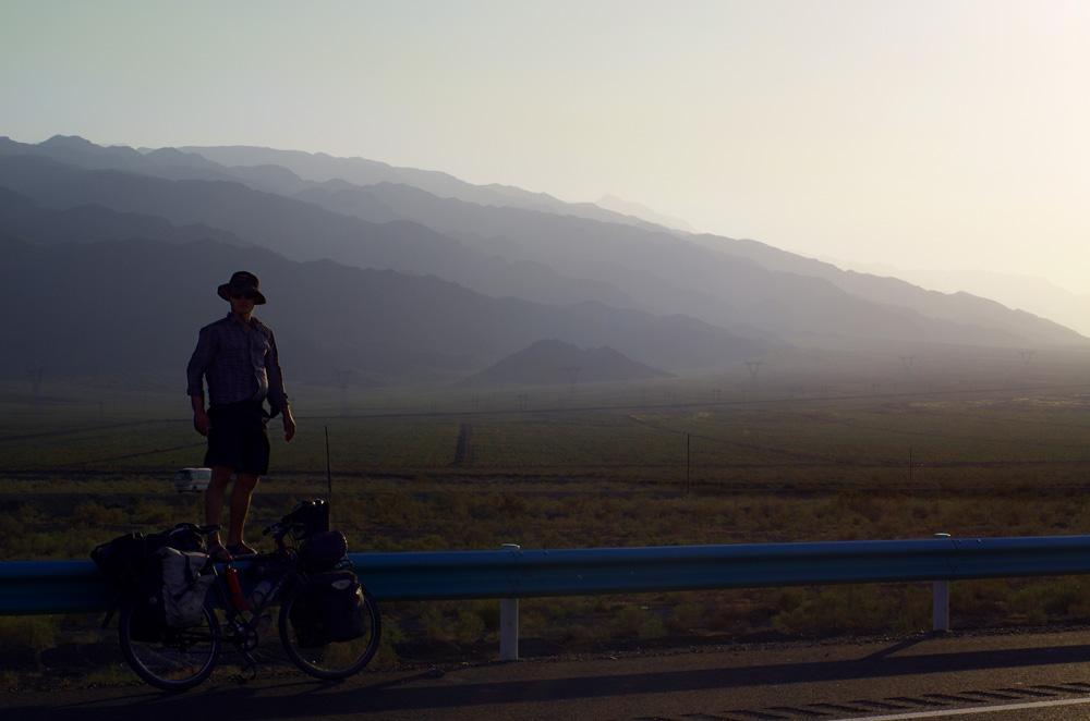 Brian prend la pause pour l'objectif alors que se profilent devant nous les montagnes de la chaîne des Monts Tian que nous allons traverser le lendemain.