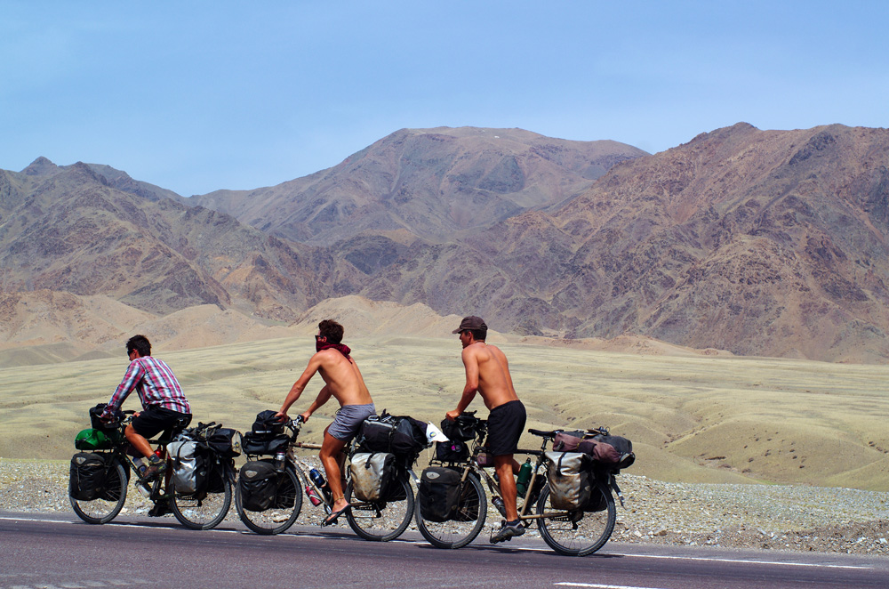 Les 650 km jusqu'à la frontière kazakhe nous font grimper à plus de 2000m d'altitude où nous retrouvons un paysage assez proche de ce que nous pouvions voir sur les hauts plateaux de Bolivie. La région est aride et les vents sont froids, la terre se transforme en un sable fin allant du jaune au rouge-orangé et nous devons parfois parcourir plusieurs dizaines de kilomètres dans ce décor avant de trouver un bâtiment synonyme d'eau et de nourriture pour nos corps fatigués. L'ambiance est bonne dans l'équipe. Nous sommes heureux d'avoir retrouvé une certaine liberté et de pouvoir enfin rouler sans être des hors la loi comme nous l'avons été dans le Sichuan : http://solidream.net/solidfilm-no30-asie-chine-objectif-4000m-dans-lancien-tibet/