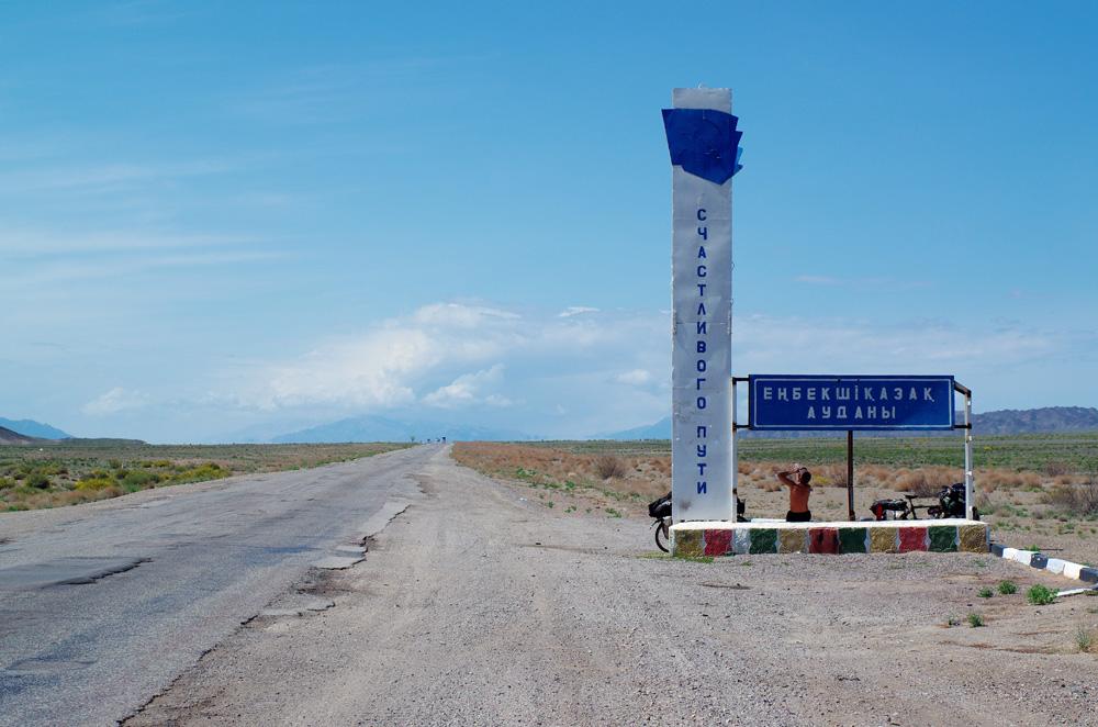 Les premiers kilomètres au Kazakhstan sont une succession de traversées de grandes steppes faisant paraître des sommets enneigés en arrière-plan. La différence avec la Chine est aussi qu'il y a bien moins d'endroits où se ravitailler. Du coup, nous revenons à la base : les pauses se font sur le bord de la route en cherchant le peu d'ombre qui s'offre à nous.