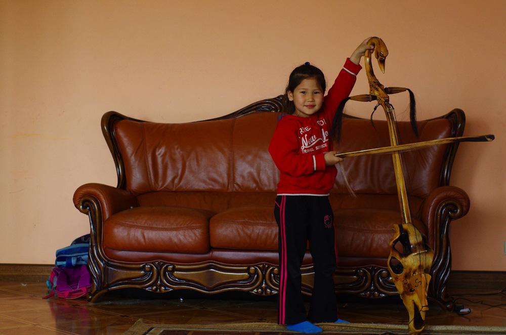 Cette petite fille vient de Mongolie, d'Oulan Bator plus exactement, et vit à Almaty avec ses deux frères et ses parents qui nous accueillent chez eux pour quelques jours. Elle est fière de nous montrer les instruments venant de son pays. Celui-ci est en bois, c'est un objet de décoration, mais son père nous explique qu'ils sont normalement en os et diffuse ainsi un son exceptionnel.