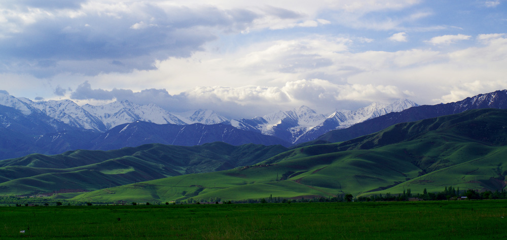 Le Kirghizstan après avoir passé les premières montagnes : une large plaine verte avec une grande chaîne de sommets enneigés en fond. C'est là bas que nous allons nous évader...