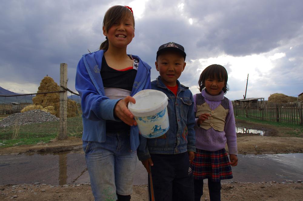 """Ces trois enfants nous présentent un des mets locaux : """"l'ayran"""". Ou plus simplement du yaourt, un produit originaire d'Asie Centrale d'ailleurs. Attention, rien à voir avec les pots que l'on pourrait trouver au supermarché ! Ici, c'est frais et en bon européen on peut trouver ça un peu fort. Mais avec un peu de sucre, on se régale."""
