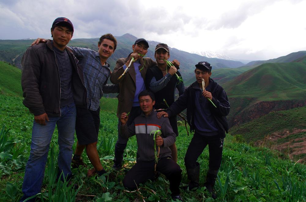 Puis, après la récréation, Jamchibeck et Jorobeck, arrivés en 4×4 une heure plus tôt, nous emmènent sur le flanc de la montagne exposé ouest, à environ quatre kilomètres de la maison. Nous sommes neuf dans la voiture et la bonne humeur bat son plein. Le véhicule s'arrête, tout le monde sort en direction des grandes étendues vertes. Nous les suivons. Ils nous expliquent comment trouver à manger dans ces montagnes, nous pointant du doigt les plantes que l'on peut manger. Nous cueillons ces racines au goût légèrement amer et nous asseyons tous ensemble sur les bords de cette arène naturelle.