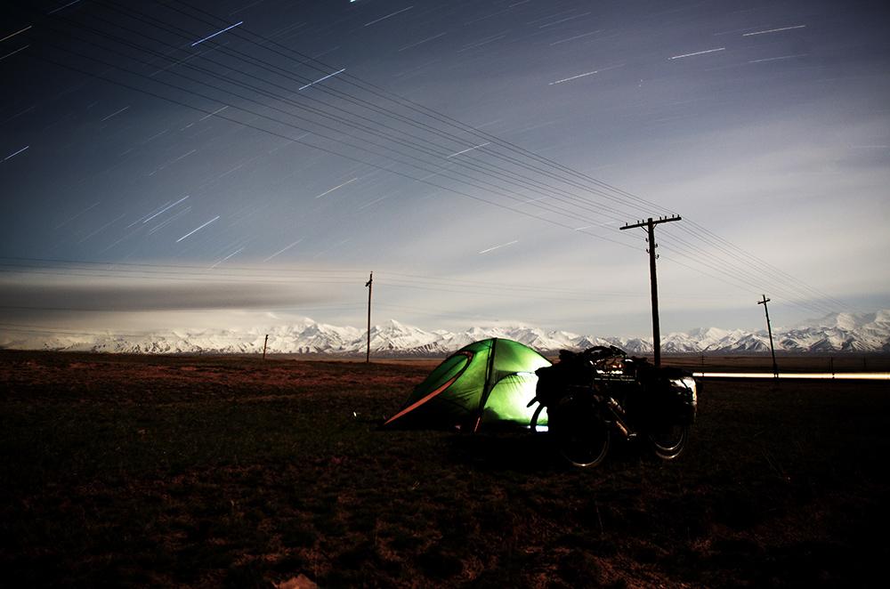 Photo à longue exposition sur une vingtaine de minutes. Nous passons la nuit à environ 3100 m près de Sary-Tash après s'être bien réchauffés dans un petit resto et dégusté une cuisse de poulet avec petits légumes après les 2350 m de dénivelé positif effectués ce jour. Nous nous endormons sous un ciel scintillant que la clarté d'une telle altitude nous rend d'autant plus magique. Le croissant de lune éclaire les montagnes du Tian Shan qui forment la frontière naturelle avec le Tadjikistan.