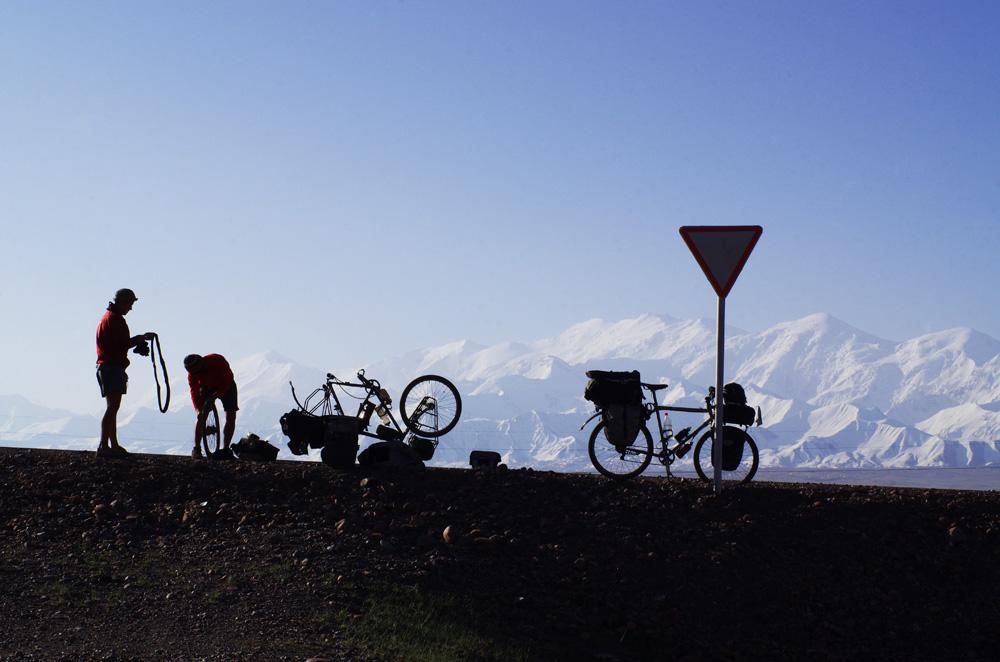 Nous devons encore descendre une longue vallée avant de pouvoir passer la frontière. Le lendemain, nous admirons le pic Lénine qui culmine à 7134 m. La journée est assez pénible avec un fort vent de face qui remonte l'air chaud de la vallée vers les hauteurs. On ne peut pas gagner à tous les coups… Ajoutez à ça un Siphay fiévreux, un début de tendinite au genou pour Brian et quelques crevaisons, notre longue descente vers le paradis tadjik prend des allures de descente aux enfers, malgré le décor magnifique.