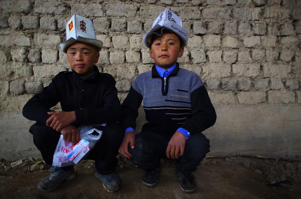 """La pluie semble se calmer. Nous disons au revoir aux petits jeunes qui nous ont guidé jusqu'au terrain de volley et reprenons la route vers la frontière... Comme beaucoup d'hommes, ils sont fièrement coiffés du chapeau traditionnel le """"ak-kalpak"""". Il ne protège pas vraiment du froid ni du soleil, mais il est à la mode pour certains."""
