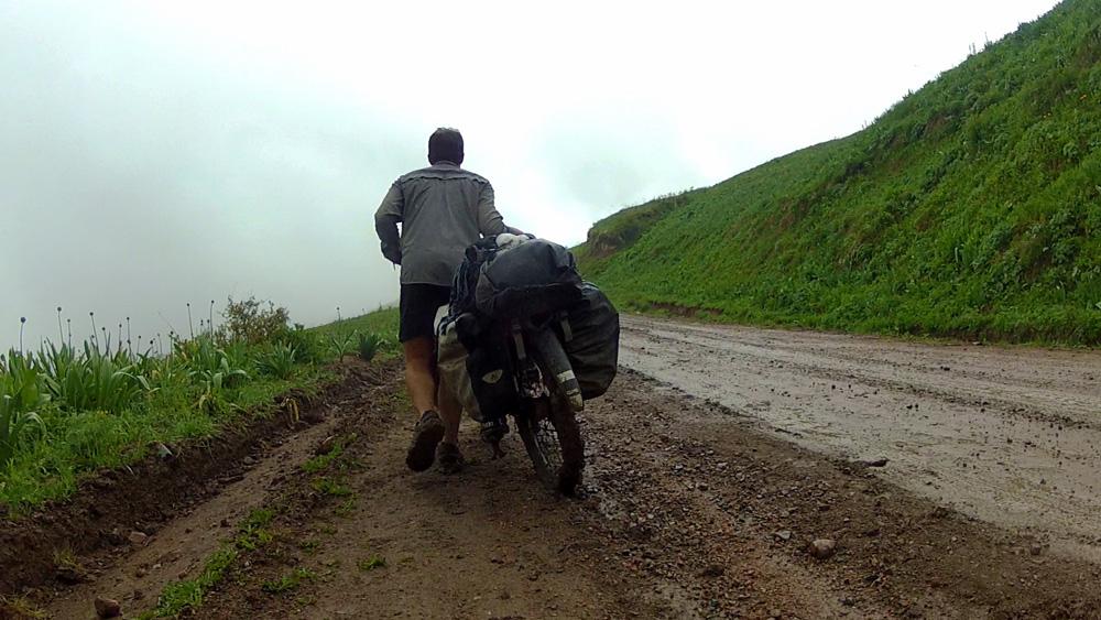 La terre mouillée devient notre tortionnaire. Pousser nos vélos devient un enfer. Nos pieds glissent, nos chaussures amassent à leur tour des kilos de boue et nous nous transformons en de gros patauds en train de pousser un engin ressemblant vaguement à un vélo. Dans cette piste en lacets nous faisons du sur place. Brian, exténué comme les copains, tente même de couper à travers champs pour s'épargner des calvaires de la piste. L'effort est rude mais il gagne un peu de terrain et économise quelques kilos de gadoue.