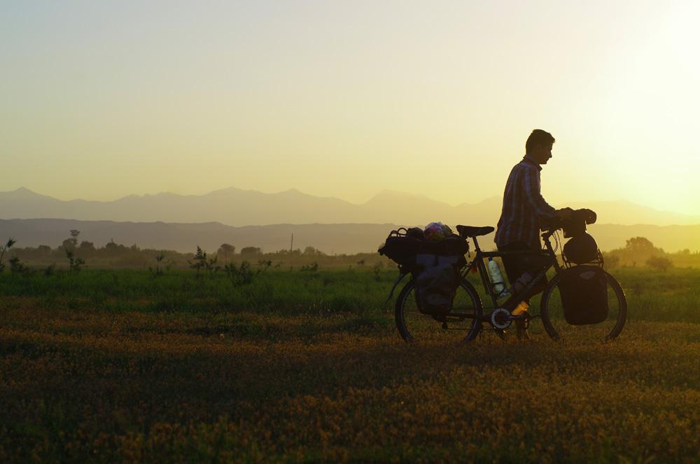 Dans ces débuts sur les routes du Caucase, la température est encore très haute en journée. Nous sortons de nos duvets tôt le matin pour commencer « à la fraîche », se reposer à l'ombre ou dans un café aux heures chaudes, puis finir le soir avec quelques dizaines de kilomètres. Ici, Brian sort du champ où nous avons établi le camp la veille au soir.