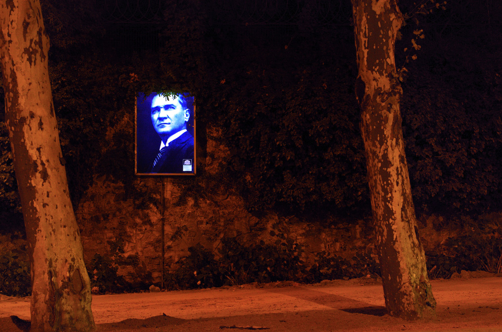 Portrait Mustafa Kemal Atatürk, le père de la Turquie moderne. C'est la radicalisation, l'amalgame entre la religion islamique et le gouvernement laïc, et la vision capitaliste que le gouvernement et son premier ministre Tayyip Erdogan affiche publiquement qui pousseront les gens à sortir dans les rues. L'interdiction d'acheter de l'alcool après 22h et la réduction du délai pendant lequel un avortement est autorisé viennent s'ajouter à des projets où les bénéfices financiers potentiels viennent écraser les notions culturelles, de bien être, d'écologie et d'esthétique : construire un grand centre commercial à la place d'un des rares parcs de la ville, le parc Taksim Gezi.
