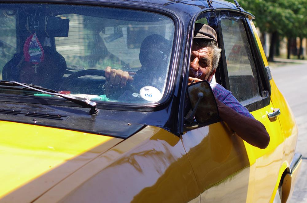 Ici aussi nous intriguons les gens au volant de leurs voitures. A défaut d'accrocher la photo de leur président ils suspendent une croix à leur rétroviseur. L'Homme a besoin d'un guide.