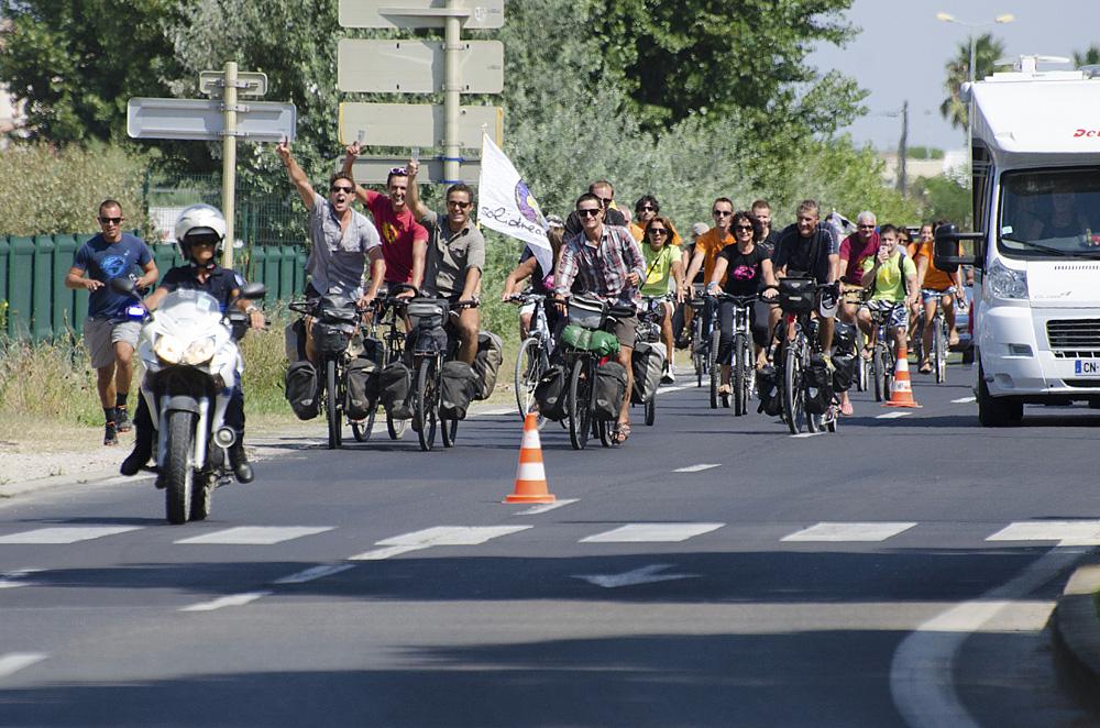 Nous passons un premier rond-point où une quarantaine de personnes nous acclament, montent sur leurs vélos et nous suivent pour la dernière ligne droite. Certains courent tandis que d'autres pédalent. Ils nous accompagnent physiquement pour la première fois. Nos cœurs se serrent, nos gorges se nouent, nous parlons moins… Il reste 500m, nous apercevons la foule, les banderoles, les bras levés… le bruit des cornes de brume, des sifflets et des applaudissements qui sont de plus en plus forts.