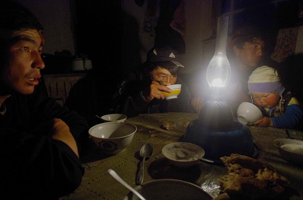 Le 15 mm grand angle permet de capturer, même dans une scène relativement obscure, l'ambiance d'un repas à l'intérieur d'une petite cahute.